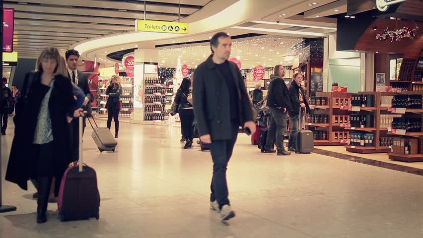 LONDON, ENGLAND - 06 DECEMBER 2015: International travelers walking in the airport hall -  Crowd walking at the Heathrow airport, England - 1080p