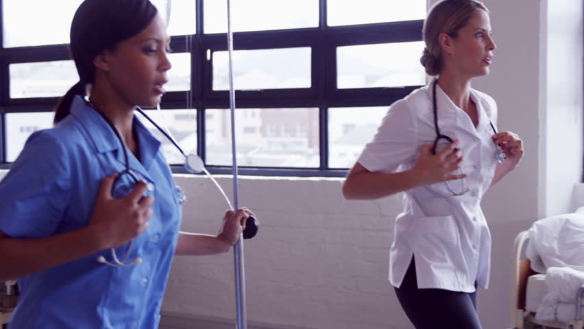 Doctor and nurse running together with intravenous drip