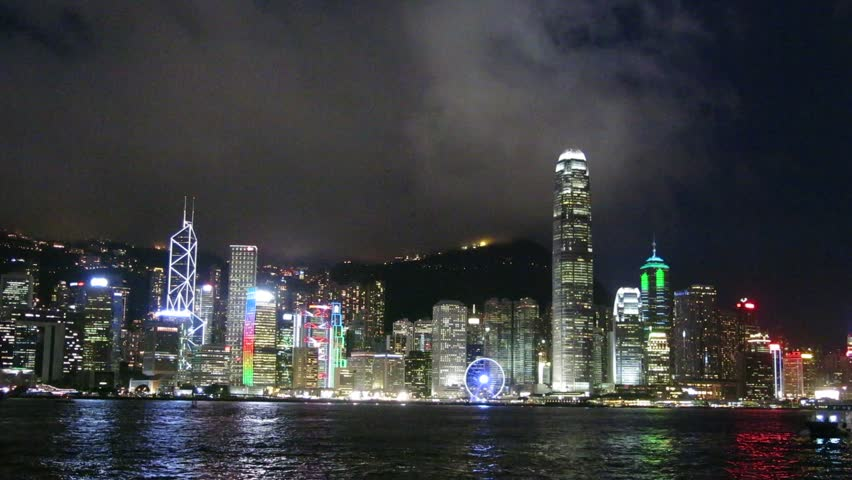 Hong Kong, China – August 13, 2015: Skyscrapers and light display at night in Victoria Harbour of Hong Kong. Junk boat is in the harbour.