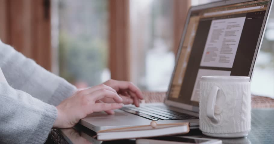 Woman hands typing in a document on a laptop keyboard. Slow Motion 4K, DCi. Female hands working on computer in cozy room. Searching information, using text editor, reading, studying, freelance.