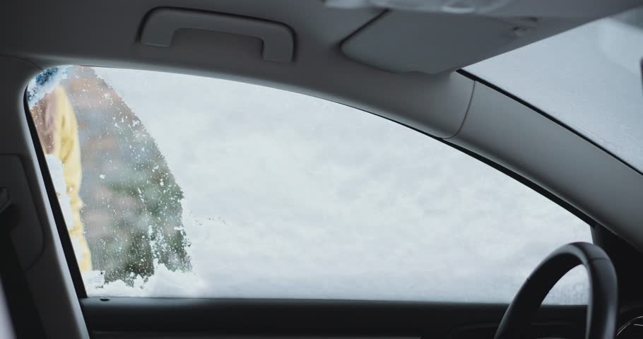 Young woman cleaning Snow and Ice off her Car wind shield window. Slow Motion, 4K DCi. Unrecognizable Woman brushes off the snow from parked car. Winter snow storm, safe driving, weather challenge.