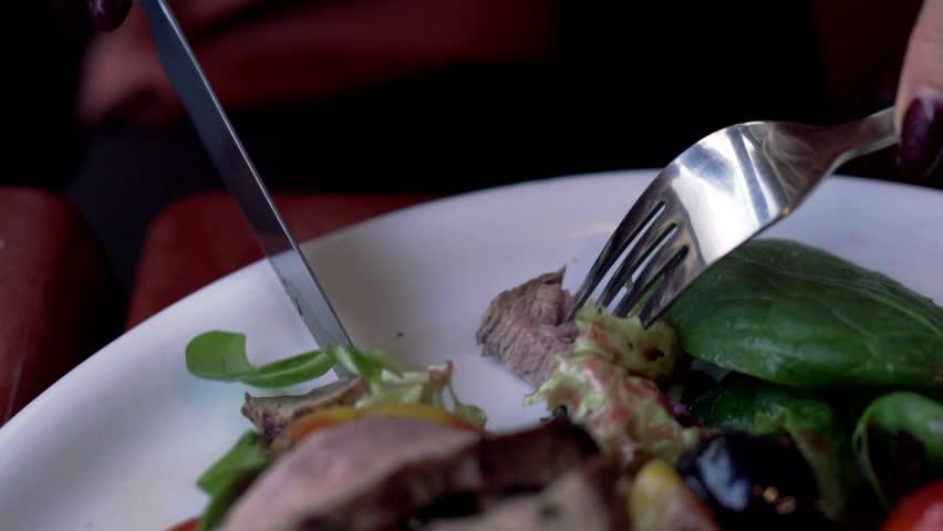 Female hands eating tasty salad in restaurant