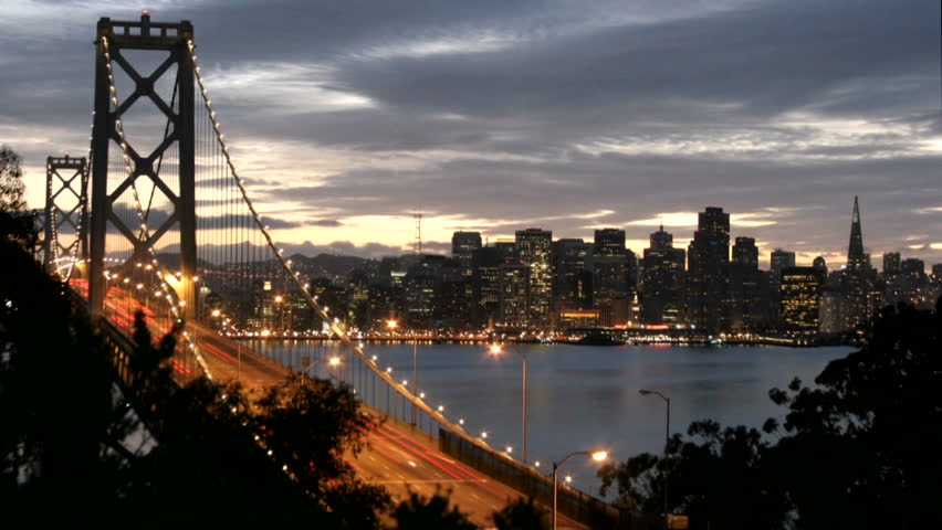 San Francisco's Oakland Bay Bridge grows brighter as darkness falls over the city skyline.