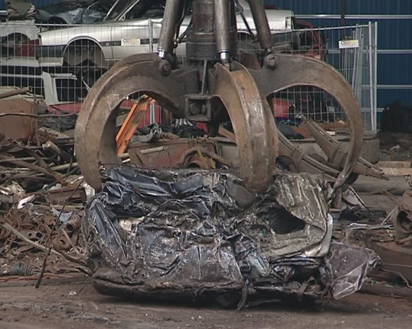 Pressed piece of car handling with special machine. Scrap metal. Industrial junk.