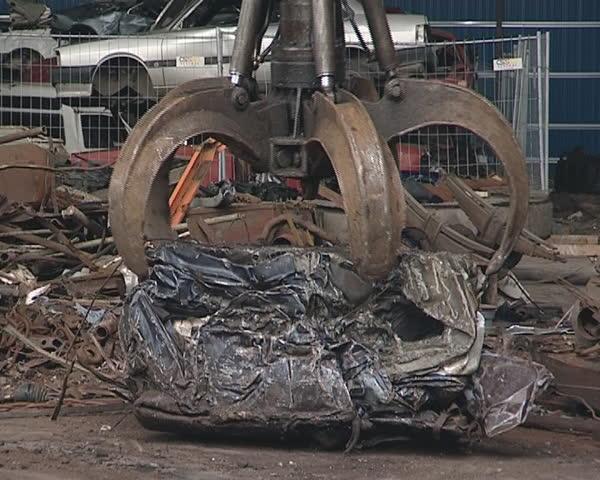 Pressed piece of car handling with special machine. Scrap metal. Industrial junk.