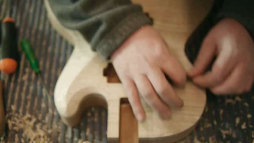 Hands of young man at work as craftsman in italian workshop with guitars and musical instruments. Dolly shot - HD stock footage clip
