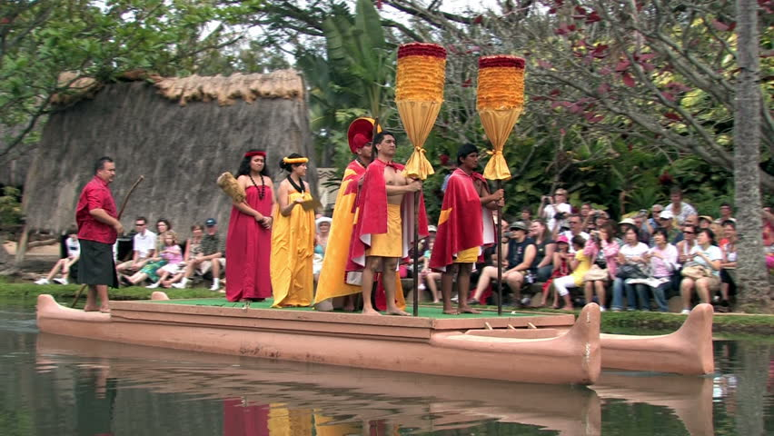 Polynesian Cultural Center in Laie Oahu Hawaii. Canoe show with dancers. Demonstration for tourists in main lagoon. Orange and red skirts on Royalty. Water, lagoon and palm trees. - HD stock footage clip