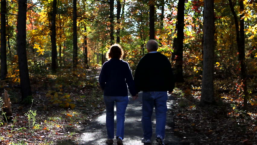 Mature loving couple walks down a pathway in the woods in autumn. They are bundled up for the cold. - HD stock footage clip