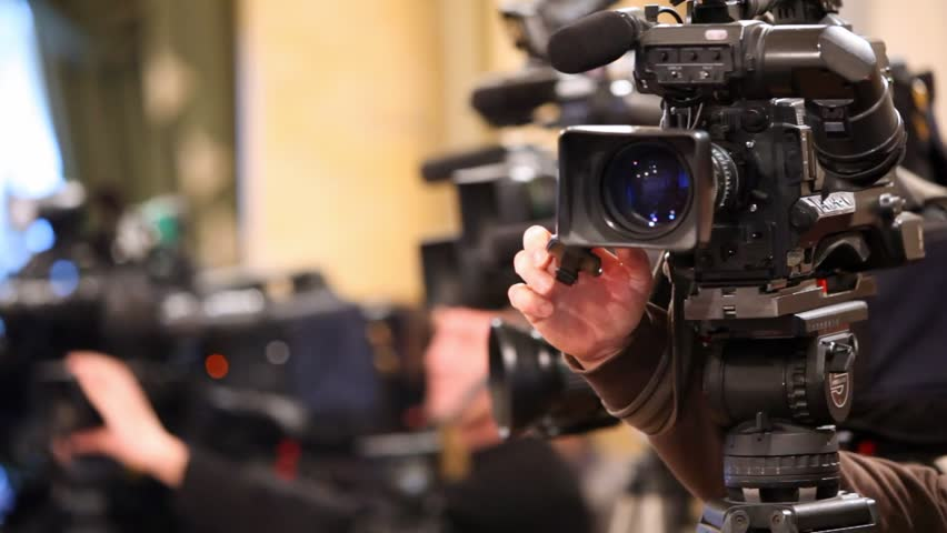 Videocamera and hands of operator, adjusting its close up