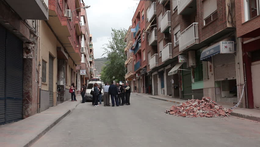 LORCA, SPAIN - MAY 20, 2011: Earth quake destruction in Lorca, Spain on May 20, 2011, several days after event. Government officials having street meeting. Stabilize balcony on business.