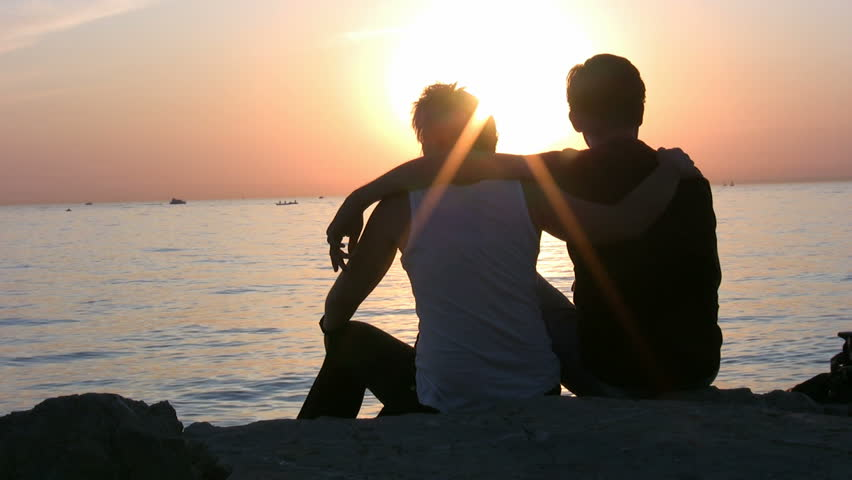 Couple Sitting In The Beach During Sunset Stock Footage