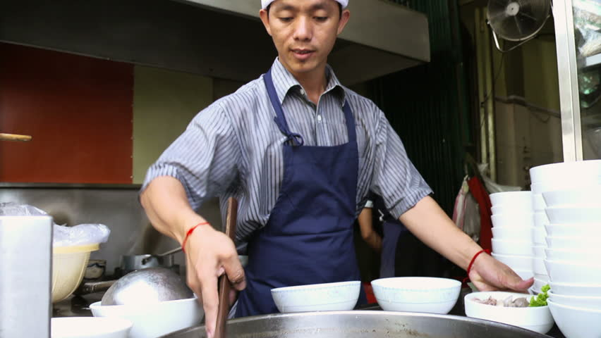 Chef preparing traditional Asian street food and working in restaurant kitchen, Phnom Penh, Cambodia, Asia. Low angle