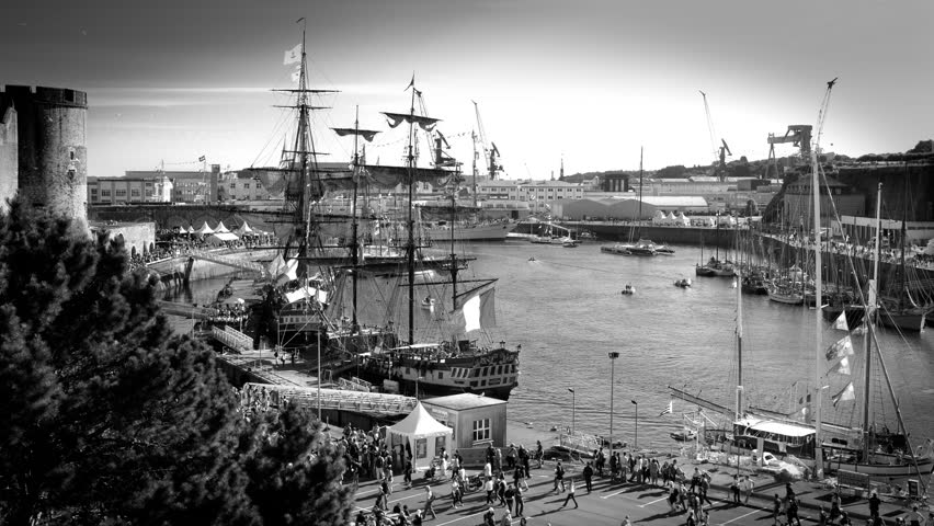 Brest, France - July 14, 2016: Brest's Maritime Festival showing old riggings of Etoile du Roy, La Fayette's ship Hermione and Cuauhtemoc in the harbor. Black and white timelapse - Penfeld river.
