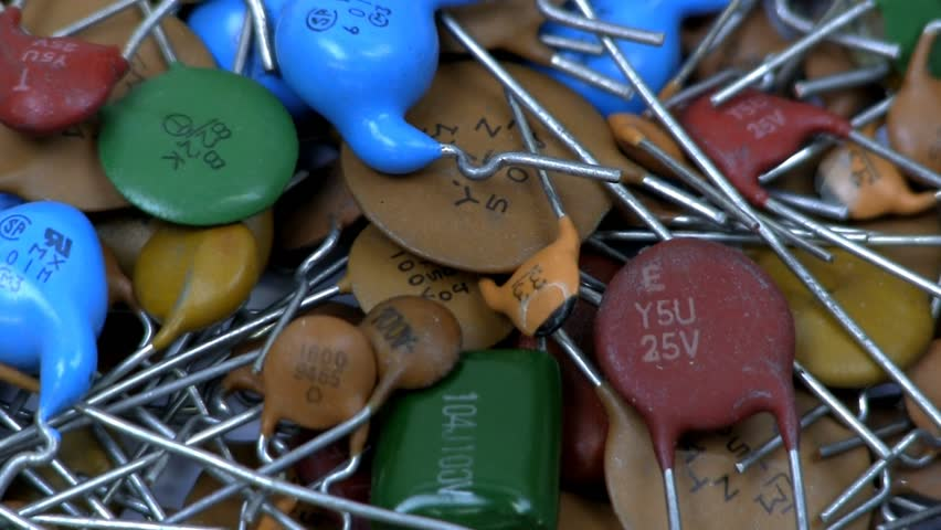 A pile of colorful through hole capacitors rotates clockwise