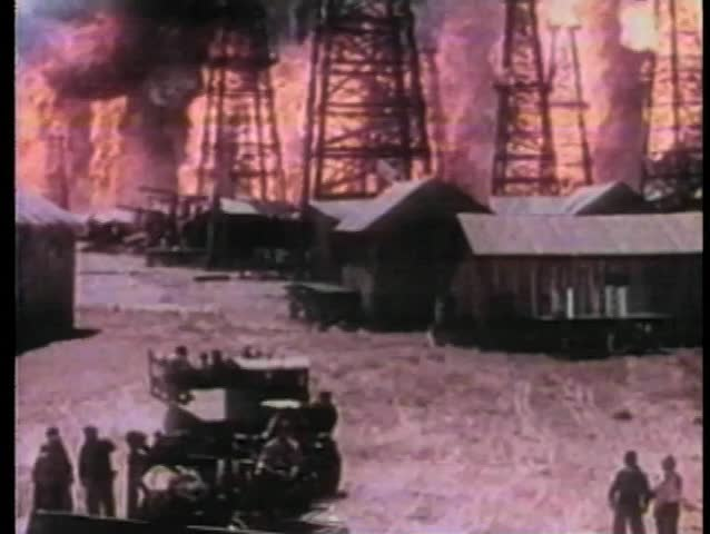 High angle view distillation tower falling during oil field fire
