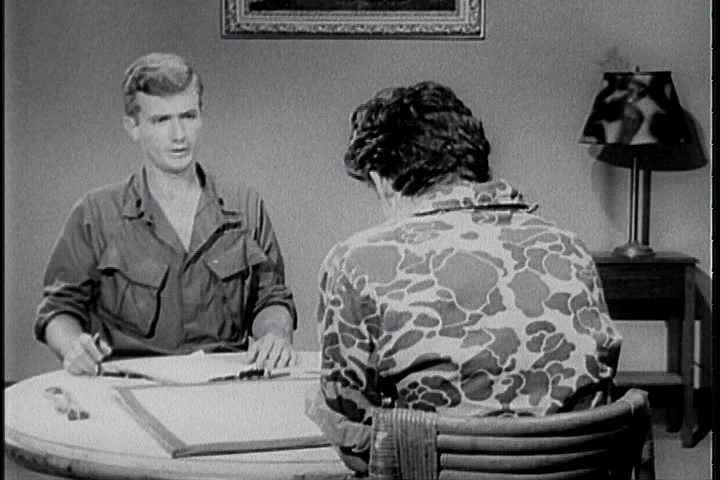Utilizing the direct approach, a United States Army interrogator interrogates an enemy soldier in a Latin American country and has him underline a position on a map in 1968. (1960s)