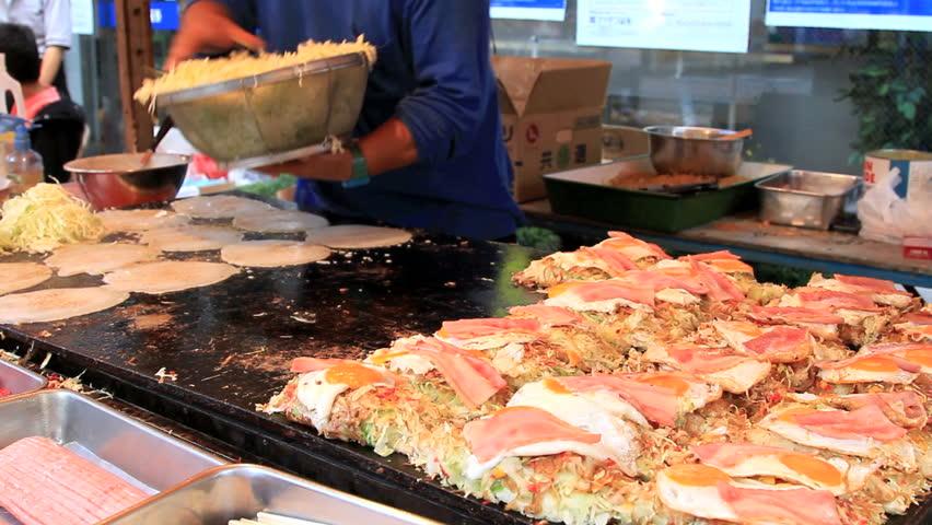 TOKYO, JAPAN - SEPTEMBER 23: Annual autumn festival in Chofu, Japan on September 23, 2011. Cooking okonomiyaki at the festival in Chofu, scene of the festival.