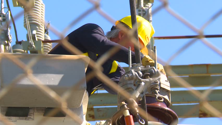 electrical worker on substation with danger sign zoom
