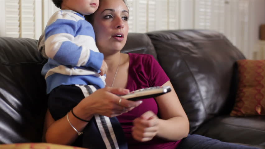 A lovely Hispanic mother with TV remote control in hand talks to her toddler about what they see on the television.