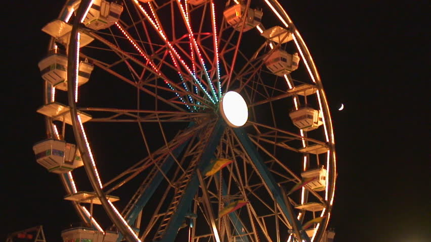 Crescent moon shines on brightly lit rotating ferris wheel - wide shot - HD stock footage clip