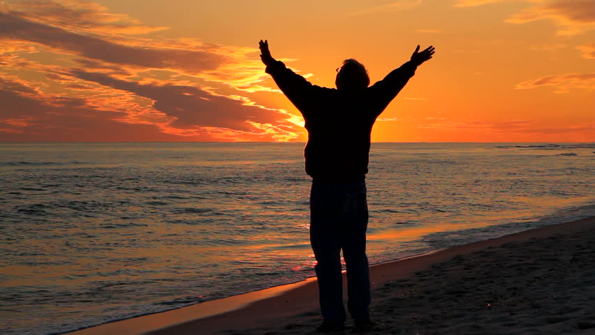Man, with arms raised toward the heavens, prays at the beach at sunset. - HD stock video clip