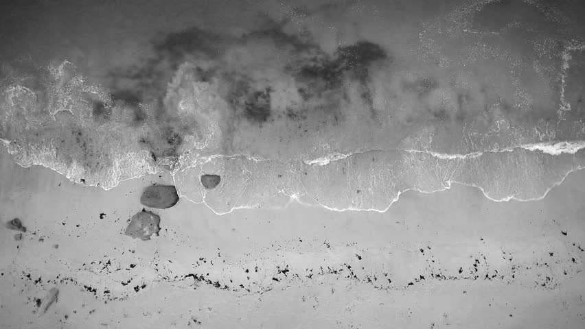 Aerial closeup - Hovering the seaside on the beach until a granite rock protrusion, then going above the sea. Elegant black and white scenery.