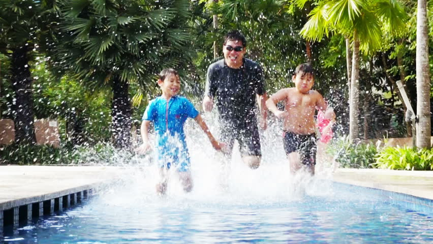 Two Asian boys racing with their father in a pool. - HD stock video clip