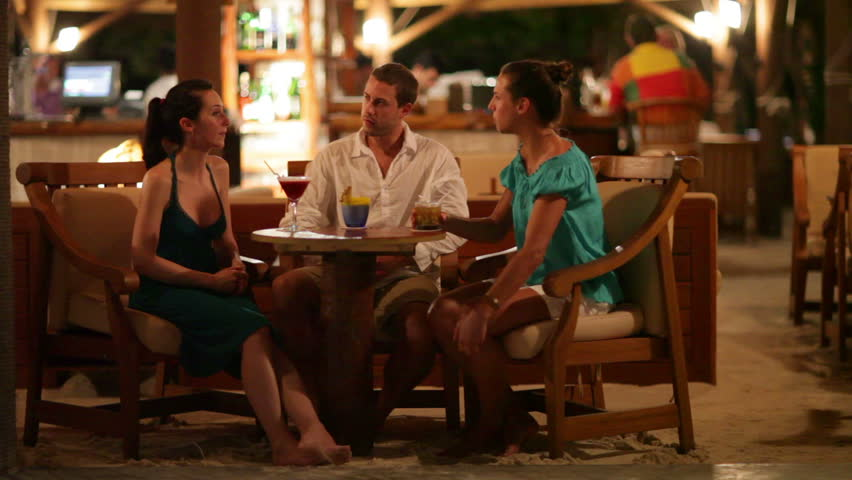 young people enjoying evening in tropical bar