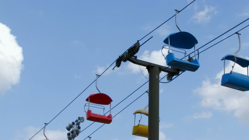 Cable Chair Lift : Cable chair lift with colored chairs against sky stock