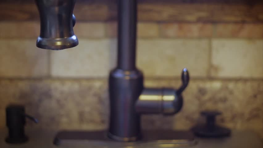 A man turns a water faucet on and off in the kitchen. - HD stock footage clip
