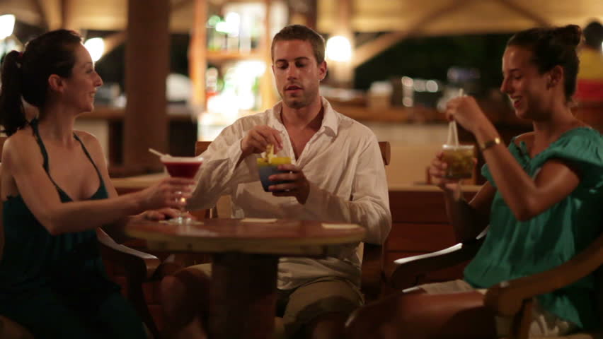 young people with cocktails enjoying vacation evening in bar