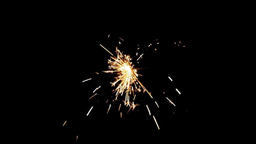 Sparkler Over Black (HD). Gun powder sparks shot against deep dark background. Ambient audio included. Slow Motion.   - HD stock video clip