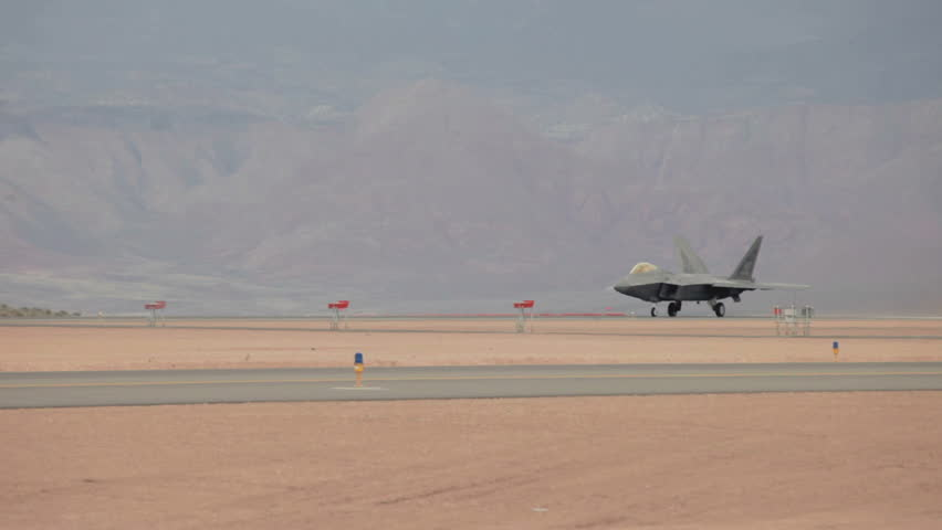 ST GEORGE, UTAH - MARCH 17: Aircraft F-22 Raptor takeoff during airshow on March 17, 2012 in St. George, Utah. Wind with blowing sand in desert. Skilled pilot demonstrating advanced air superiority of US and allied military.