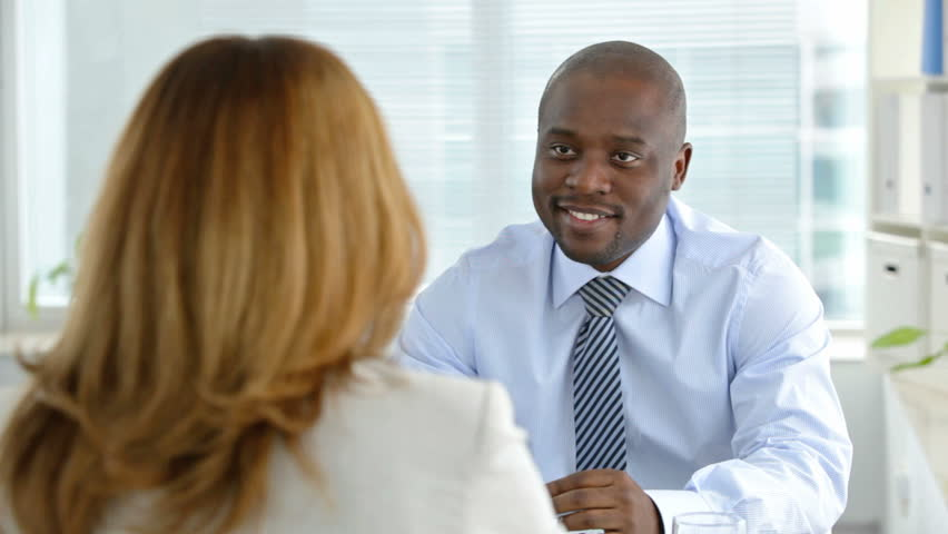 Smiling businessman interviewing a young woman for a vacant position