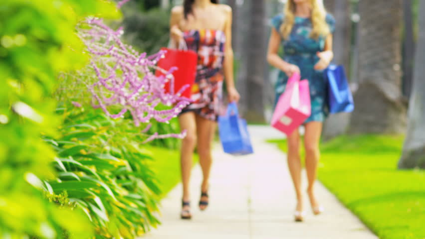 Laughing girls carrying designer shopping bags on Rodeo Drive