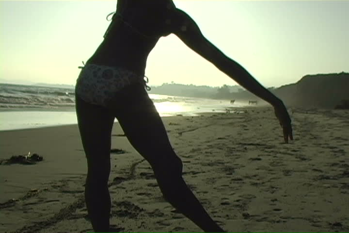 A beautiful, silhouetted young woman performs on the beach.   - SD stock video clip