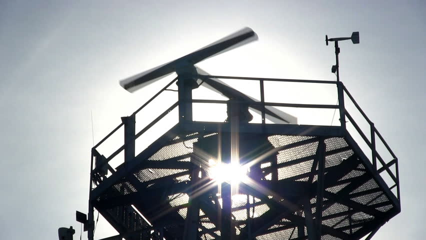 Marine traffic control radar tower silhouette close-up with spinning antenna and wind sensor  - HD stock video clip