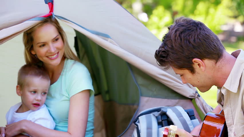 Man singing to his family while camping in a park - HD stock footage clip
