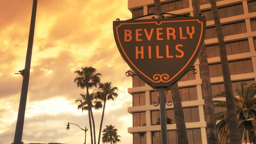 Beverly Hills, California - April 5, 2012: Traffic passes Beverly Hills Sign at Sunset, April 5, 2012 in Beverly Hills, California.