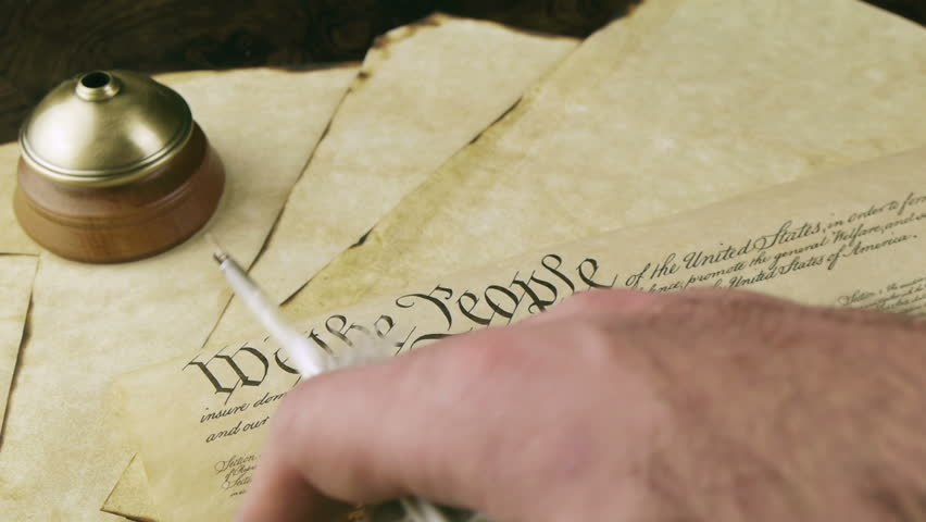 US Constitution Hand Reading (HD). US constitution parchment with feather quill shown with a male hand slowly reading as camera tilts down.