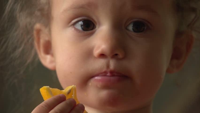 Cute little girl eating an orange, close up