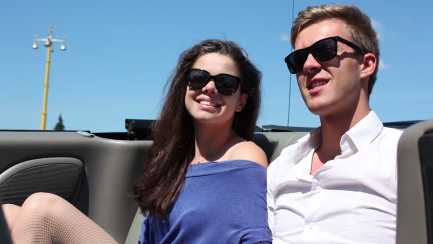 Young couple in sunglasses sit and talk in cabriolet at sunny summer day - HD stock video clip