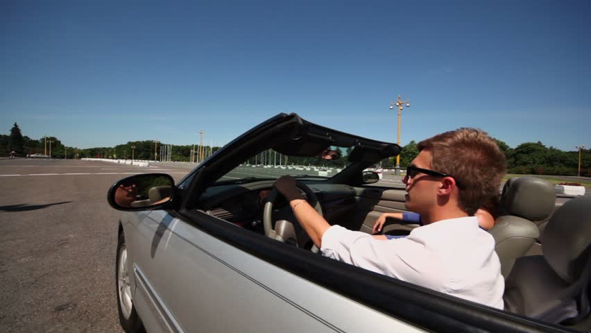 Young couple ride in cabriolet by road at sunny summer day, sideview in motion - HD stock footage clip