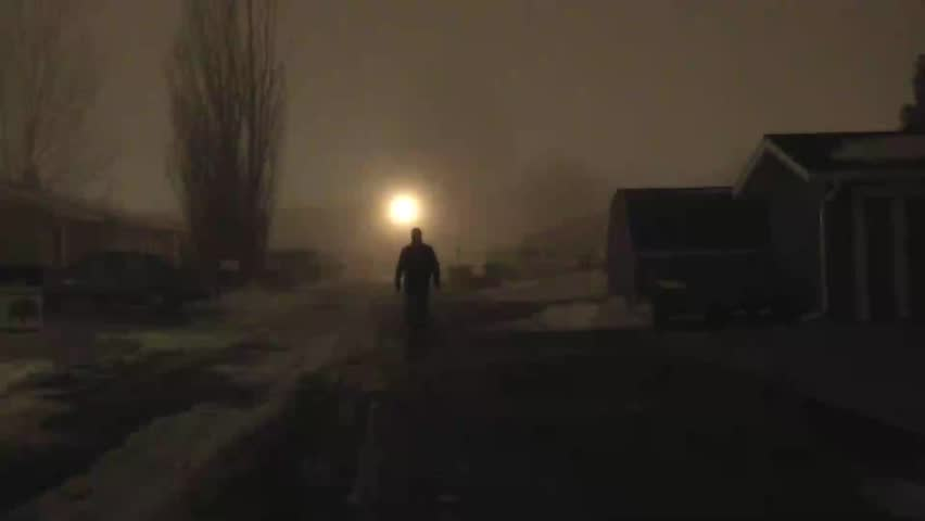 Unidentifiable actor, dark dressed man, approaching camera slow and steady in eerie fog, set at night, and in a narrow alley.