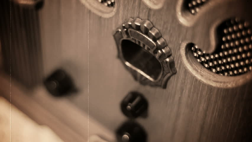 Turning an old-fashioned radio.  Shallow DOF.  Old, scratchy film look.