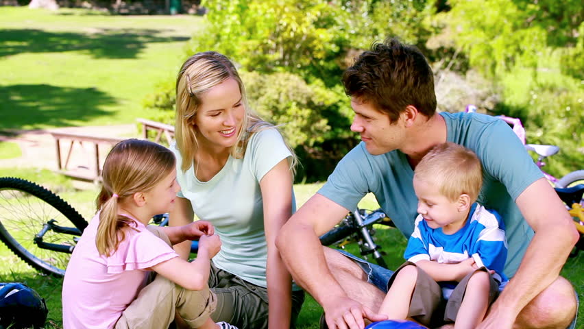 Family with bikes sitting in a park - HD stock video clip