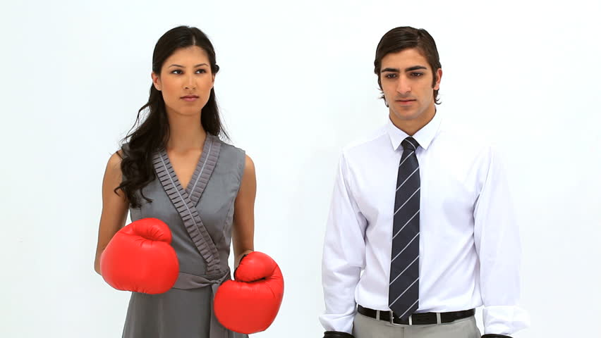 Woman wearing boxing gloves alongside her colleague against a white background - HD stock footage clip