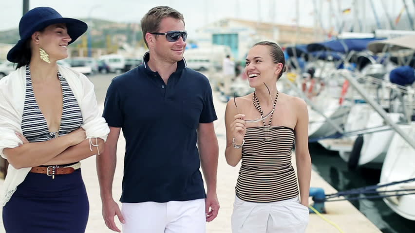 Young rich friends walking and talking in marina