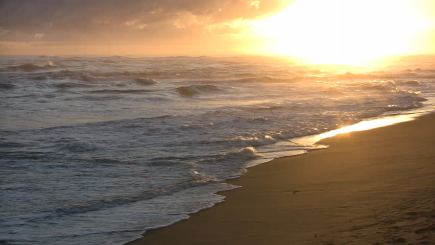 Waves gently wash up onto the beach, then recede as the sun starts to rise. (High Definition) - HD stock video clip