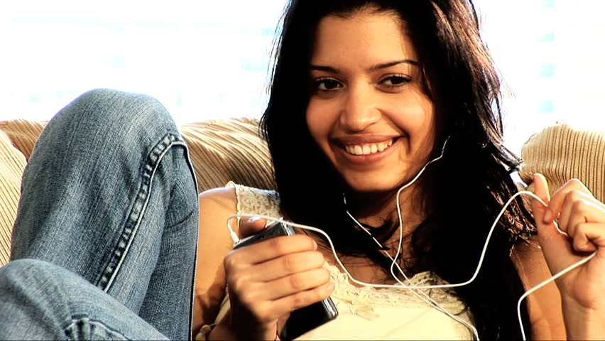 Beautiful latino girl relaxes at home with her mp3 player - HD stock video clip